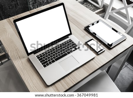 Tablet, phone and laptop on desk - stock photo