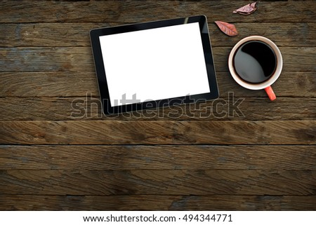 Tablet showing Blank Screen and Coffee red cup top view on wooden table background