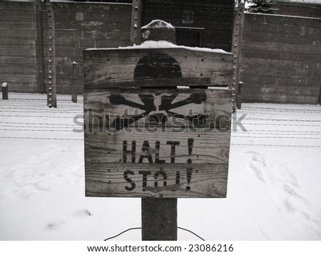Tablet STOP! infront of barbed wire under tension in Auschwitz - stock photo