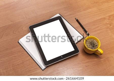 Tablet. Tablet with blank white screen and coffee cup on office wooden table - stock photo