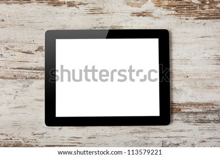 tablet touch computer gadget with isolated screen on a background of wood. - stock photo