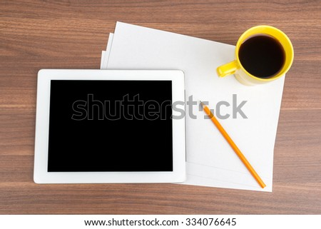 Tablet with blank paper and coffee on wooden table
