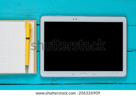 Tablet with blank screen and notepad with pen on office wooden table - stock photo