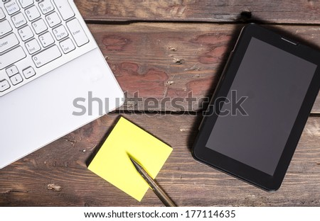 Tablet with blank screen, laptop keyboard and sticky notes on wooden table - stock photo