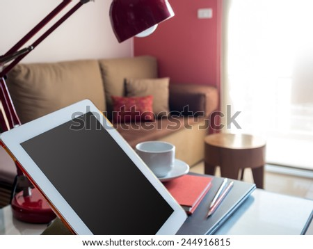 tablet with blank screen on desktop in bright modern office - stock photo