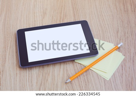 Tablet with blank screen on wooden table. Office desk mock up - stock photo