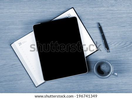 Tablet with blank white screen and coffee cup on office wooden table - stock photo