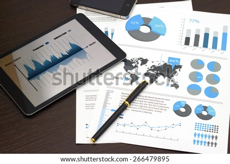 Tablet with business charts, pen, on a wooden table.  - stock photo