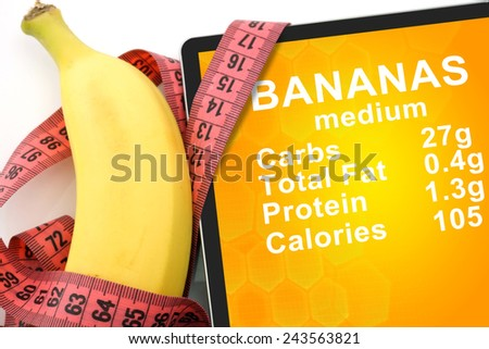 Tablet with Calories In banana  and measuring tape on white background. nutrition facts - stock photo