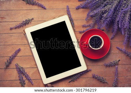 Tablet with coffee on the wooden table