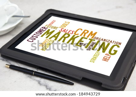tablet with CRM marketing word cloud - stock photo