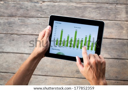 tablet with green chart in hands of business man - stock photo