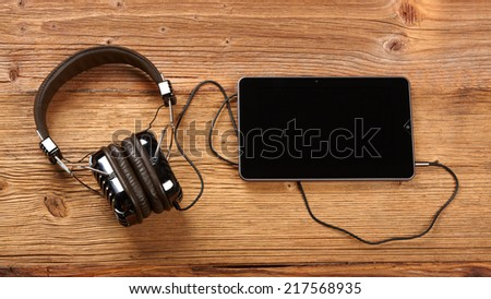 Tablet with headphones on old wooden desk.  - stock photo
