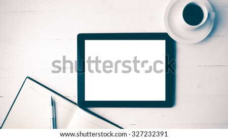 tablet with notebook and coffee cup over white table vintage style