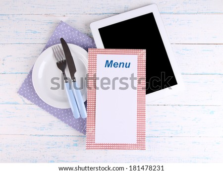 Tablet with plate and cutlery on wooden background