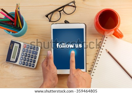 Tablet with text inside follow us on the table with offee,glasses and notebook - stock photo