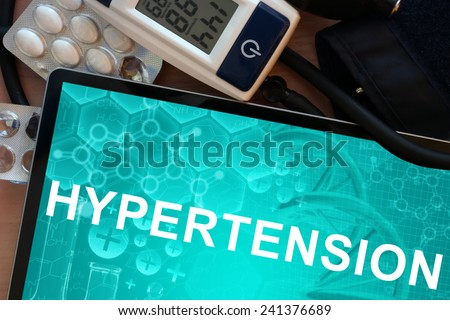 Tablet with the diagnosis hypertension and Electronic blood pressure monitor - stock photo