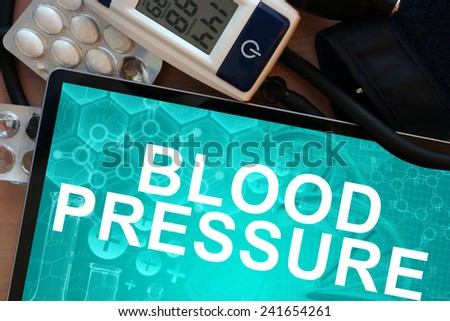 Tablet with the words blood pressure  and Electronic blood pressure monitor - stock photo