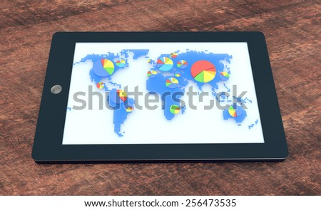 Tablet with world map and pie charts on screen on wooden office desk - stock photo