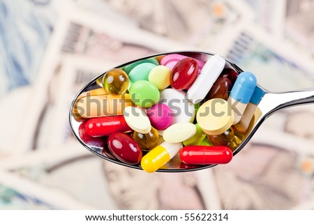 Tablets and Japanese Yen currency symbol for health costs - stock photo