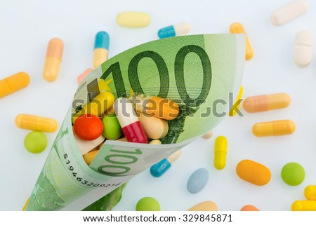 tablets and one hundred euro banknote symbol photo: cost of medicine and drugs in the pharmaceutical industry - stock photo