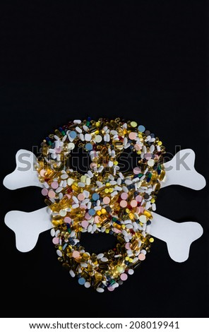Tablets, pills and capsules, that shape a creepy skull isolated on black background - stock photo