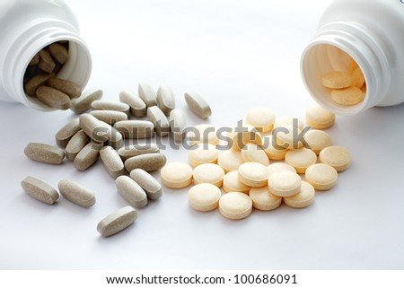 Tablets spilling out of container - stock photo
