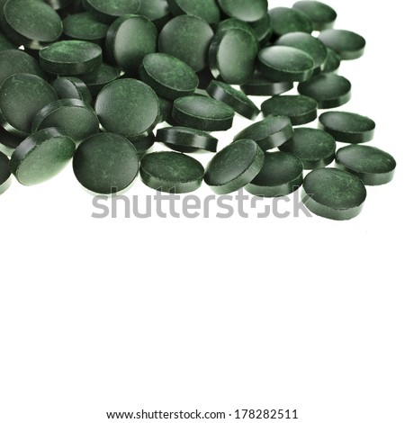 Tablets Spirulina  algae heap surface close up macro  top view, isolated on white background  - stock photo