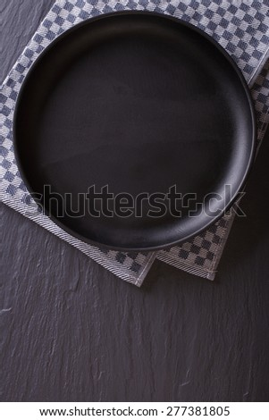 Tableware: black empty plate on the table. top view vertical  - stock photo