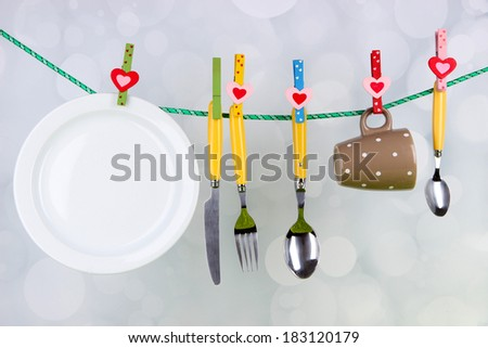 Tableware dried on rope on bright background - stock photo