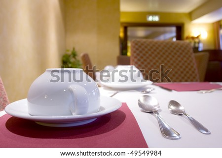 Tableware for a breakfast at an empty restaurant (white coffee cup and spoons) - stock photo