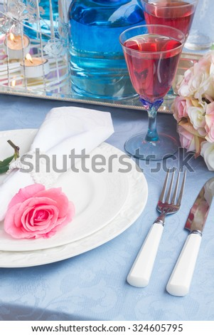 Tableware for dinner with plates, napkin, cutlery and flowers - stock photo