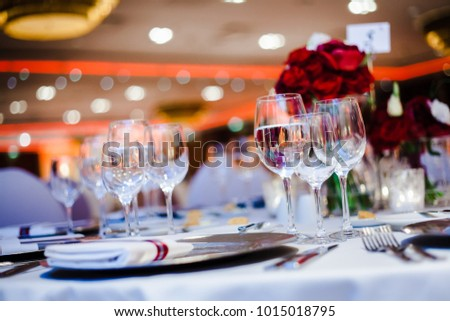 Tableware in a luxury hotel restaurant. Roses, glasses, lot of lights, dishes and cutlery.
