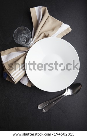 tableware on a dark background. empty white porcelain plate, beige napkin, cutlery made ??of wood, tumbler, bread. French baguette. - stock photo