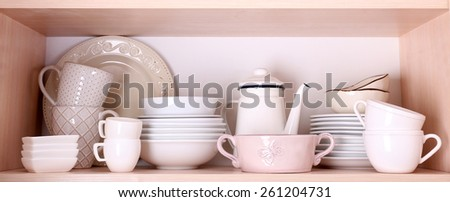 Tableware on wooden shelf - stock photo