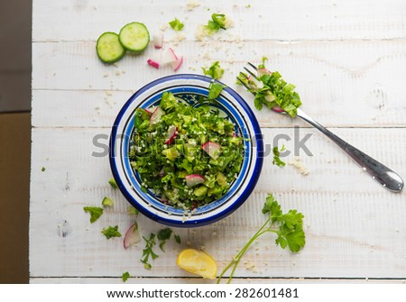 Tabouleh - a middle eastern vegetarian salad. Spilling out from a bowl. Top angle shot. - stock photo