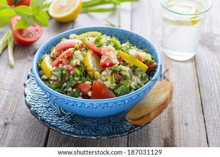 Tabouli salad in blue bowl on wooden table - stock photo
