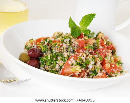 Tabouli salad in white bowl with coffee mug and glass of wine - stock photo