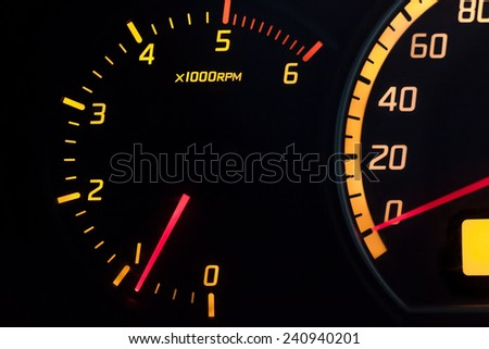 Tachometer showing the engine idling at 900 RPM. Yellow glowing dial with a red needle. Isolated against black.