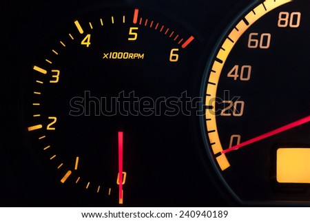 Tachometer showing the zero speed and RPM. Yellow glowing dial with a red needle. Isolated against black.
