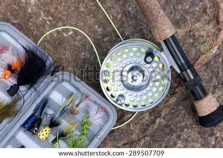 Tackle Box with flies and Fly Fishing Rod - stock photo