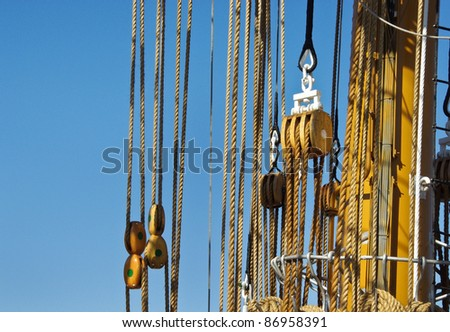 Tackles of the ancient sailing vessel. Marine ropes with wooden rigging isolated on blue background. Wooden block, pulley and ropes -  tackle on the ship. - stock photo