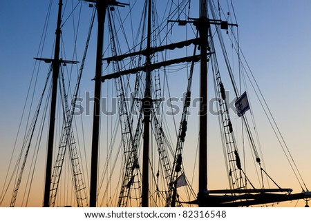Tackles sailing ship on the background of the sunset sky - stock photo
