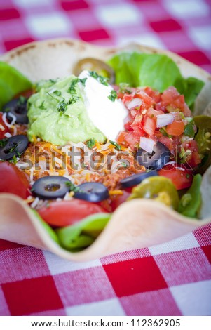 Taco salad in a baked tortilla on a tablecloth - stock photo