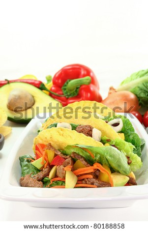 Taco shells filled with beef strips and vegetables - stock photo