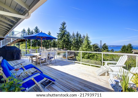 Tacoma real estate. Large walkout deck overlooking bay. Screened deck with wooden floor, deck chairs and umbrella