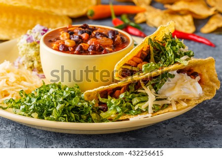 Tacos with chili con carne, salad, cheese and sour cream, selective focus. - stock photo