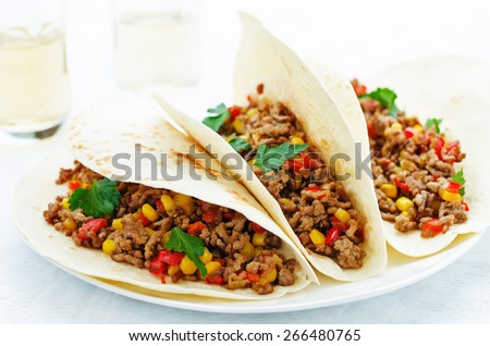 tacos with meat, corn and peppers on a white background. tinting. selective focus - stock photo