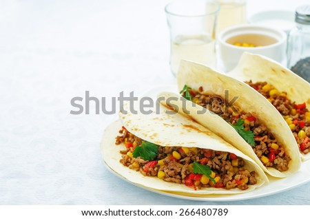 tacos with meat, corn and peppers on a white background. tinting. selective focus