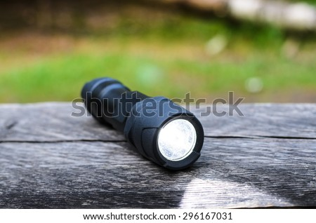 Tactical waterproof flashlight on wooden base with light beam - stock photo